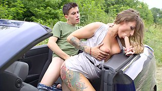 A blonde bimbo that has tattoos on her body is fucked in a car
