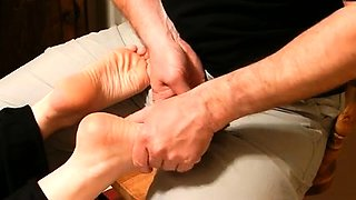 Skillful masseur working his hands on a pair of sexy feet