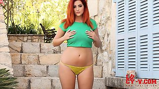 Lucy V in her green top and yellow bikini on the steps.