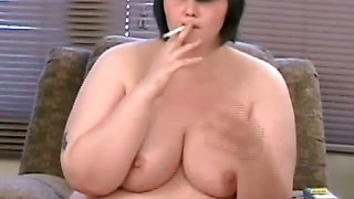 Busty brunette babe smoking nude on the sofa