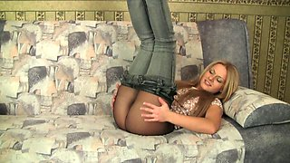 Magnificent and fresh blondie pulls down her jeans and poses on the couch