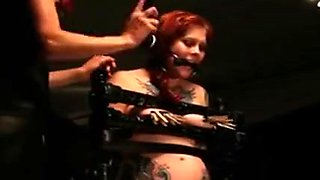 Gagged Redhead In Bondage Device Clamped And Spanked