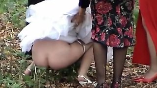 Russian bride and her bridesmaids pee in the woods