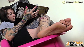 Tattoed girl puts her feet in your face